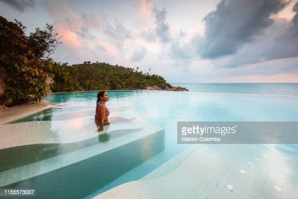 beautiful woman in an infinity pool at sunset, thailand - hotel stock pictures, royalty-free photos & images