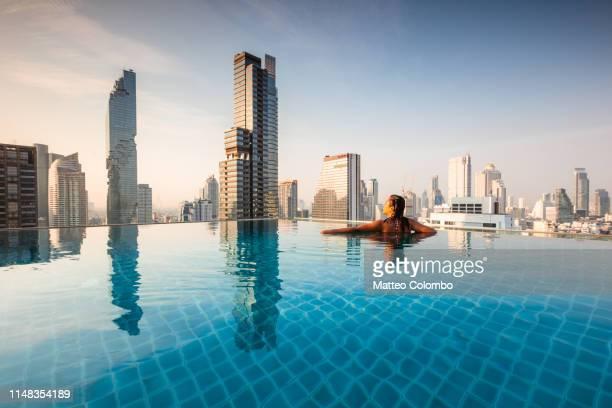 beautiful woman in an infinity pool, bangkok, thailand - bangkok stock-fotos und bilder