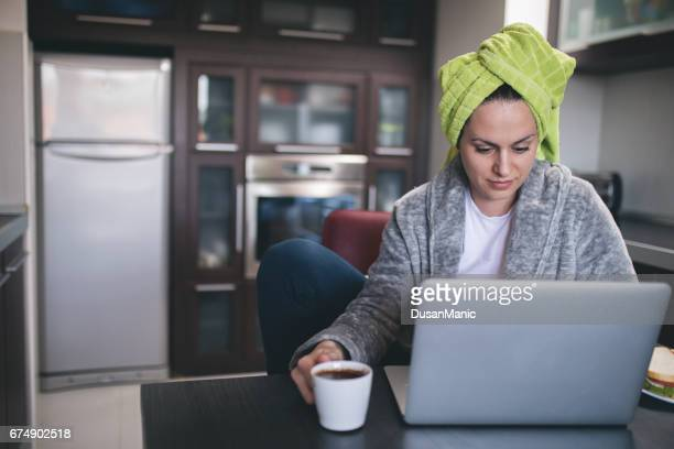 beautiful woman in bath towel using laptop - bathrobe stock pictures, royalty-free photos & images