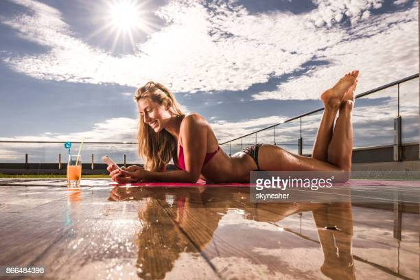 beautiful woman in biking using cell phone while sunbathing on a patio. - women of penthouse stock photos and pictures