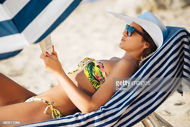 Beautiful woman in bikini at beach reading book and sunbathing