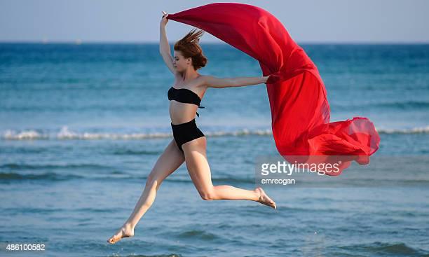 Beautiful woman in bikini in summer jumping on