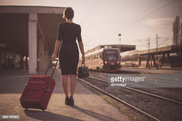 Beautiful woman in black drass carrying a suitcase traveling by train