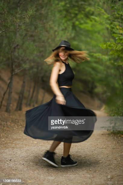 beautiful woman in black dress turning around in nature - slow motion stock pictures, royalty-free photos & images