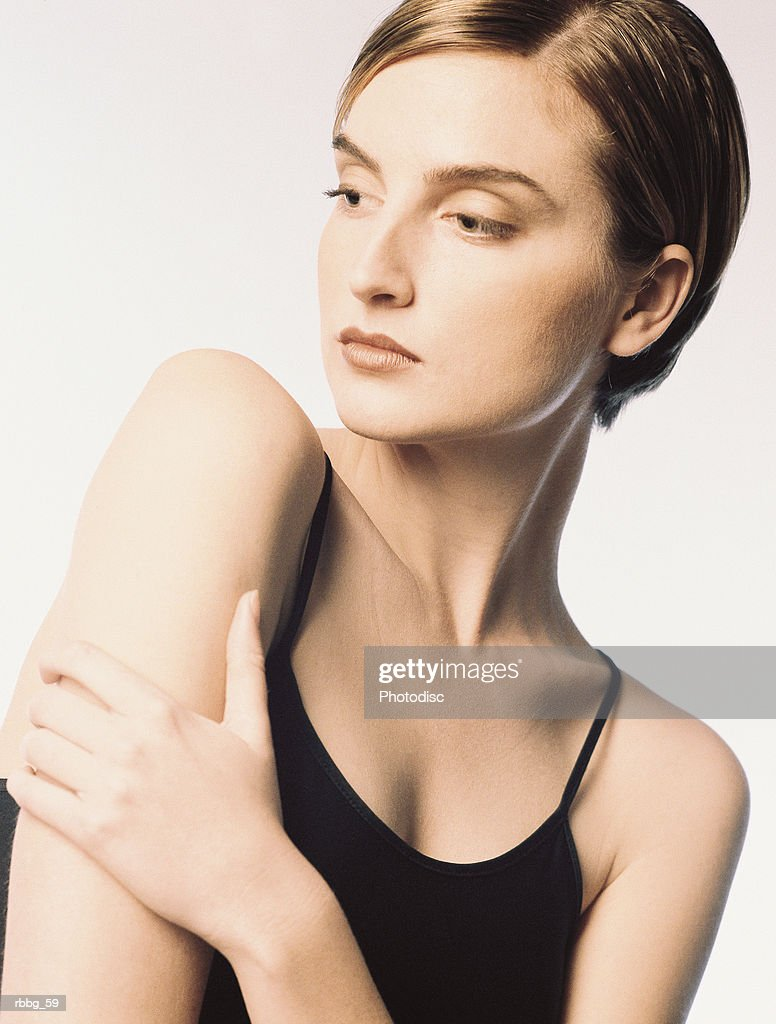 Beautiful woman in black shirt standing in a white background : Stockfoto