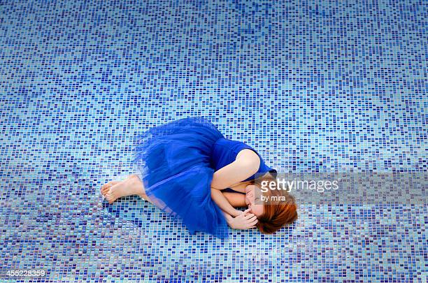 beautiful woman in blue dress lying in a pool
