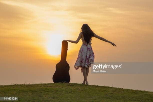 beautiful woman in bright outfit, enjoying music at sunset. - rock music stock pictures, royalty-free photos & images