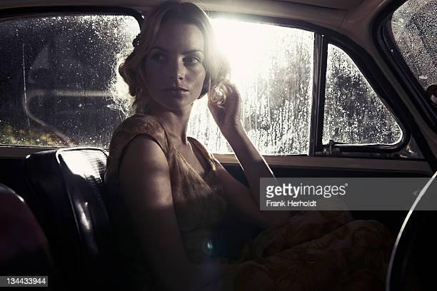 Beautiful woman in car with rain drops on windows