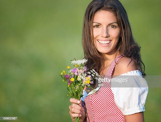 Schöne Frau im Dirndl Mode hält eine Blumenstrauß (XXXL)