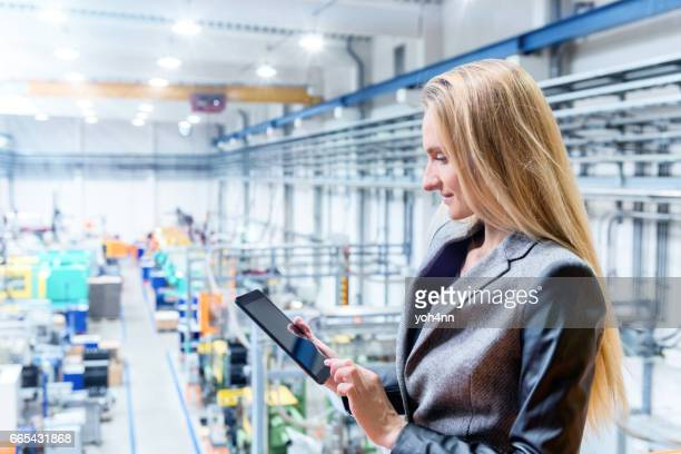 Beautiful woman in factory with digital tablet