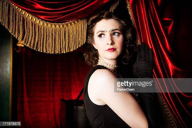 beautiful woman in front of red curtain with gold fringe - actor stock pictures, royalty-free photos & images