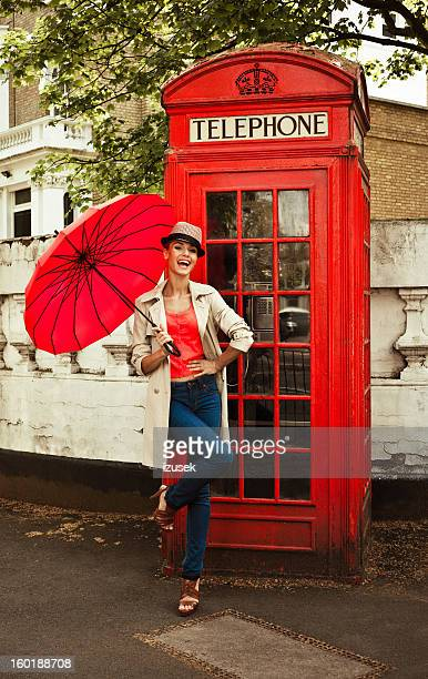 Beautiful woman in front of telephone booth