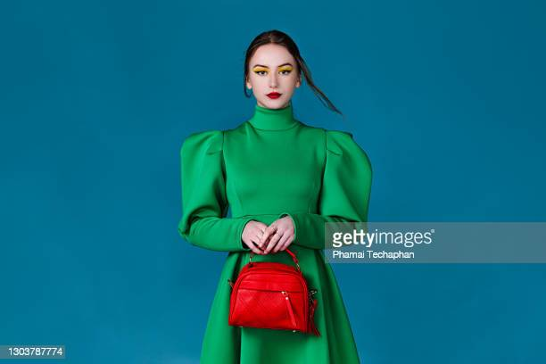 beautiful woman in green dress holding a red handbag - clutch bag stock pictures, royalty-free photos & images