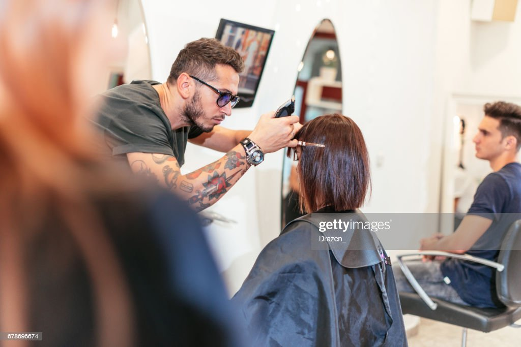 Beautiful woman in hair salon, having her hair cut : Stock Photo