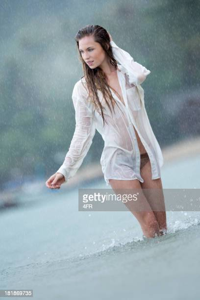 beautiful woman in heavy monsoon rain - wet shirt stock photos and pictures