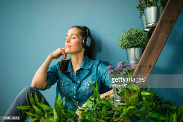 beautiful woman in her home, decorated with plants, listening music with headphones - mindfulness stock pictures, royalty-free photos & images