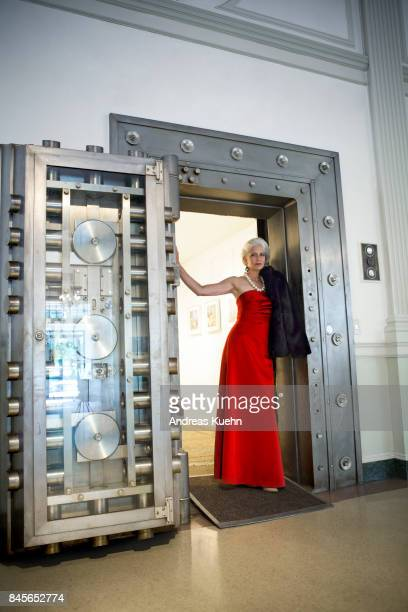 Beautiful woman in her late fifties with long, silvery, grey hair wearing a glamorous red evening gown standing at the entrance of a big metal vault.