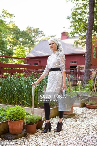 Beautiful woman in her late fifties with long, silvery, grey hair wearing a fashionable outfit and high heels with a watering can in her vegetable garden.