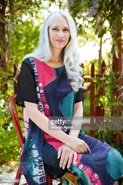 Beautiful woman in her late fifties with long, silvery, grey hair wearing a colorful outfit while sitting on a red chair in front of her flower garden.