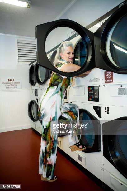 Beautiful woman in her late fifties with long, silvery, grey hair wearing modern, colorful outfit with high heels inside a laundromat.