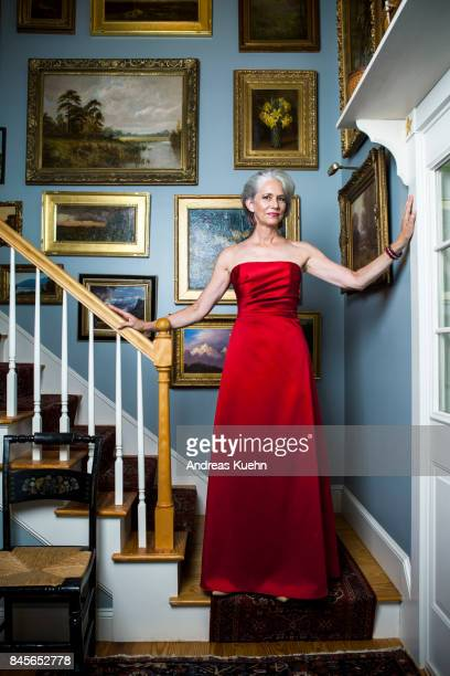 beautiful woman in her late fifties with silvery, grey hair wearing a glamorous, red evening gown while standing in a staircase in front of golden framed oil paintings. - strapless evening gown stock pictures, royalty-free photos & images