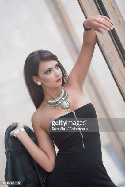 Beautiful woman in her late twenties in a little black dress and leather jacket.