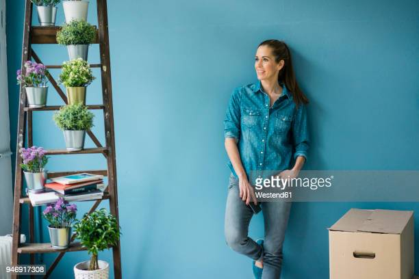 beautiful woman in her new home, decorated with plants, leaning at wall - hausdekor stock-fotos und bilder