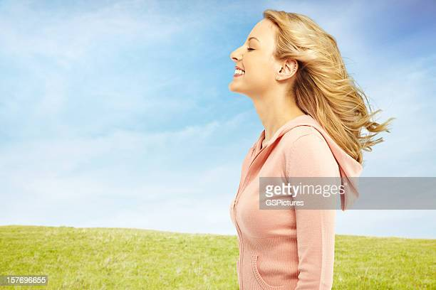 Beautiful woman in nature with the wind blowing her hair