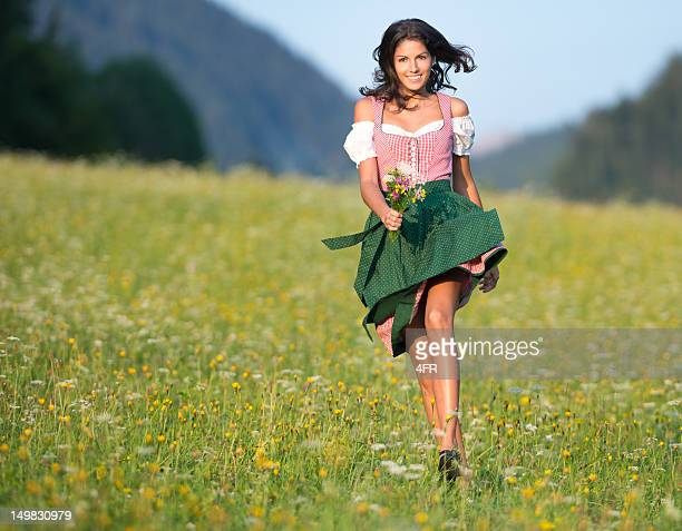 beautiful woman in oktoberfest dirndl fashion running through the meadows - traditional clothing stock pictures, royalty-free photos & images