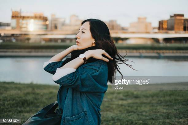 Beautiful woman in park with hair blowing in breeze