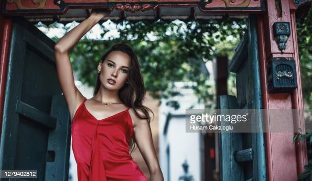 beautiful woman in red dress between doors. - red dress stock pictures, royalty-free photos & images