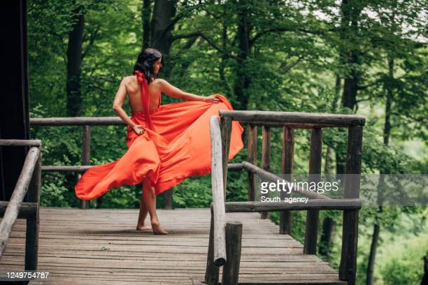 beautiful woman in red dress dancing alone in nature - red dress stock pictures, royalty-free photos & images