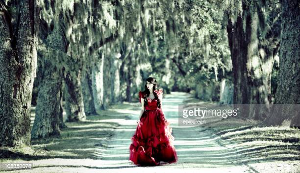 beautiful woman in red dress walking down white sand road - live oak tree stock pictures, royalty-free photos & images