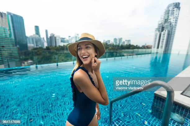 beautiful woman in rooftop swimming pool - classic blue stock photos and pictures