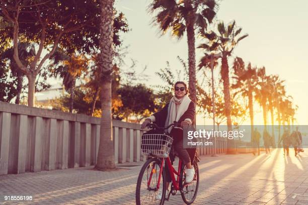 beautiful woman in spain riding a bicycle on sunset - valencia spagna foto e immagini stock