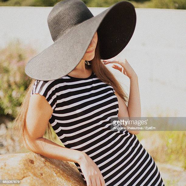 Beautiful Woman In Striped Dress Wearing Black Hat