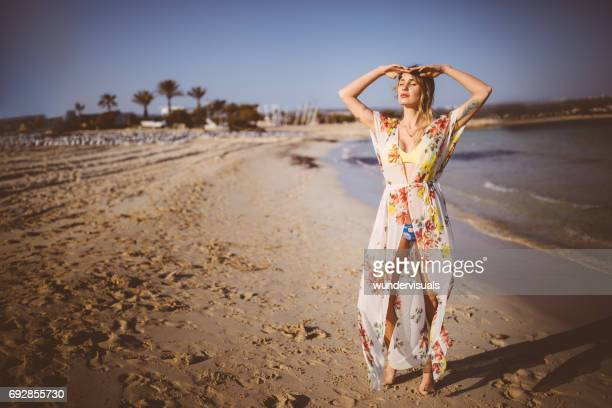 beautiful woman in swimsuit enjoying the sun by the sea - sarong stock photos and pictures