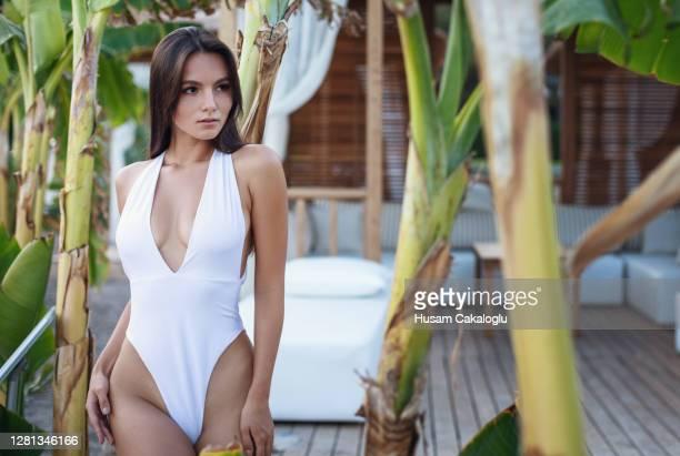 belle femme dans le maillot de bain restant parmi des bananiers par la mer. - maillot de bain photos et images de collection