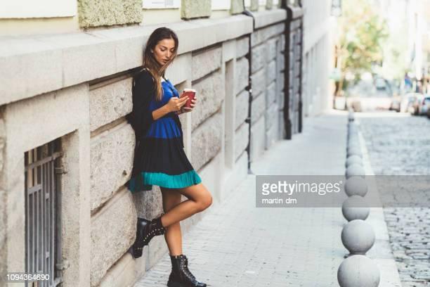 beautiful woman in the city texting - appoggiarsi foto e immagini stock