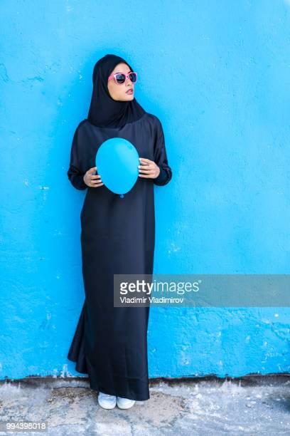 青い風船を保持伝統的な服で美しい女性