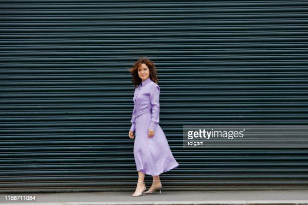 beautiful  woman in urban background - purple dress stock pictures, royalty-free photos & images