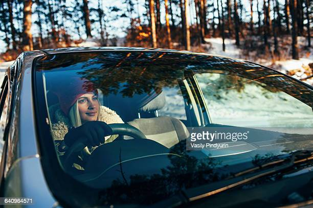 Beautiful woman in warm clothing driving car