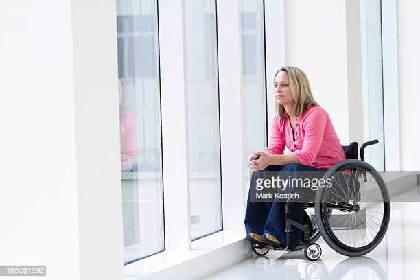 Schöne Frau im Rollstuhl mit Blick aus dem Fenster
