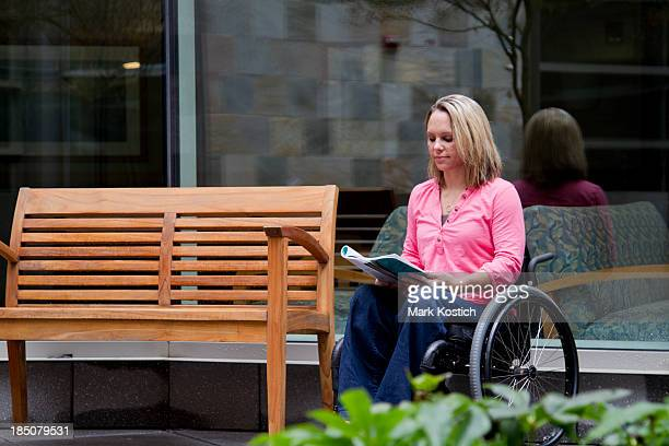 beautiful woman in wheelchair reading a magazine - paraplegic stock photos and pictures