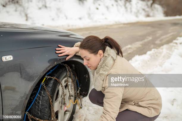 beautiful woman installing snow chain on her car - danger stock pictures, royalty-free photos & images