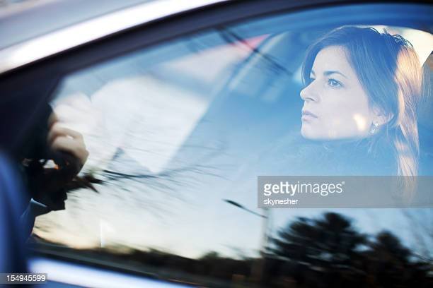 Beautiful woman is driving a car. Side view.