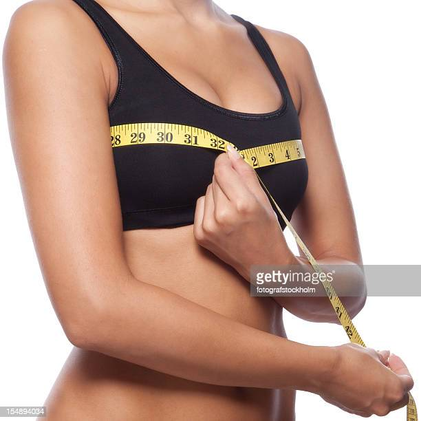 Beautiful woman is measuring her breast