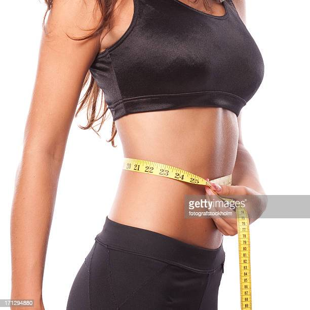 Beautiful woman is measuring her waist