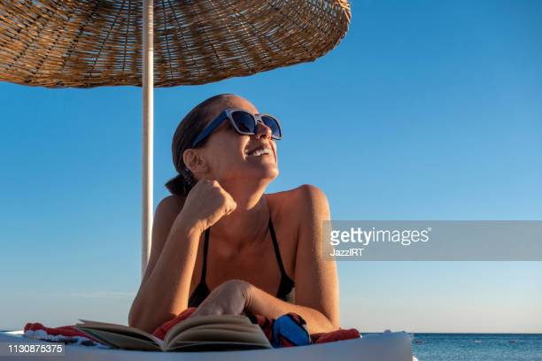 beautiful woman is reading book on the sunbed on the beach - bronzeado imagens e fotografias de stock