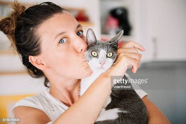 Beautiful woman kissing a cute cat at home
